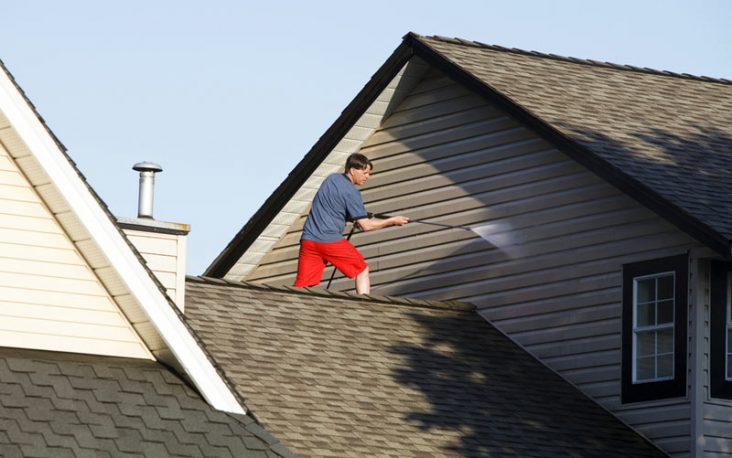 man using a pressure washing on house exterior and roof